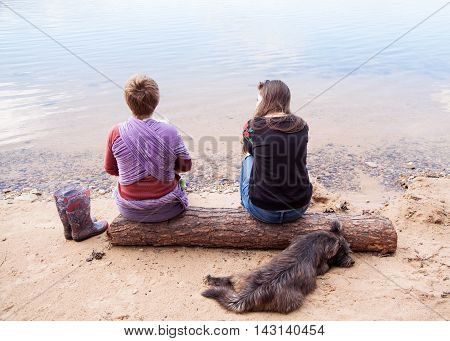 Two women are sitting on the river bench on the log a dog laying behind