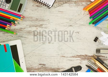 back to school frame with school supplies on aged wooden table