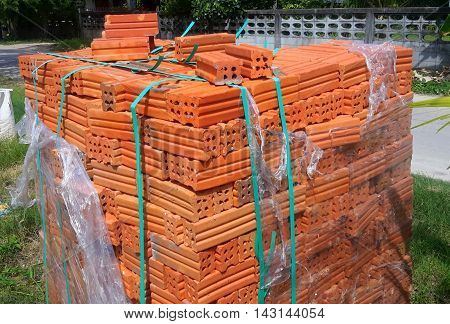 stack of red building brick partially covered with torn shrink-wrap, tied with greenish binder straps outside a hardware store near Songkhla, Thailand