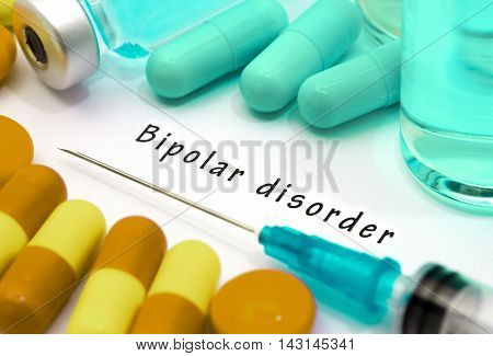 Bipolar disorder - diagnosis written on a white piece of paper. Syringe and vaccine with drugs.