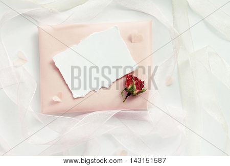 Dreamy delicate congratulation background. Pale pink paper handmade gift, empty card, dried rose, ribbons decor. Top view above, light airy mock-up.