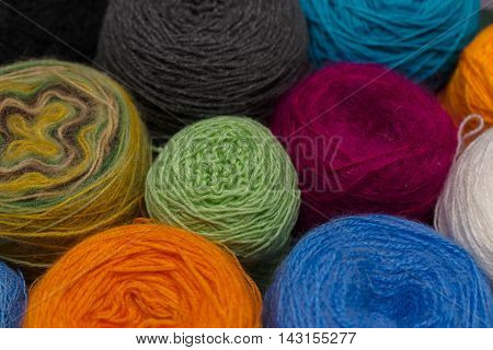 Many small balls of wool of rainbowcolors on the wooden table.