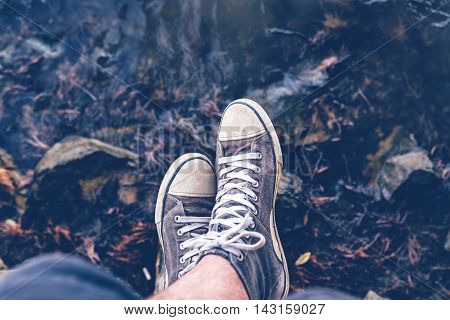 Sitting at riverbank young adult casual male legs wearing sneakers near the flowing water