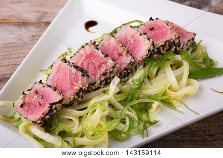 Sliced tuna meat with noodles seaweed salad
