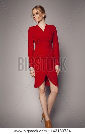 Young woman in red dress on grey background