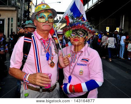 Bangkok Thailand - January 14 2014: Couple with Thai ribbons wristbands masks and hats demonstrating at the Shut Down Bangkok protest *