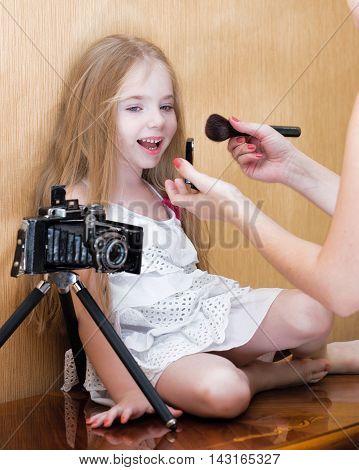Litte girl befor photo shoot near wall