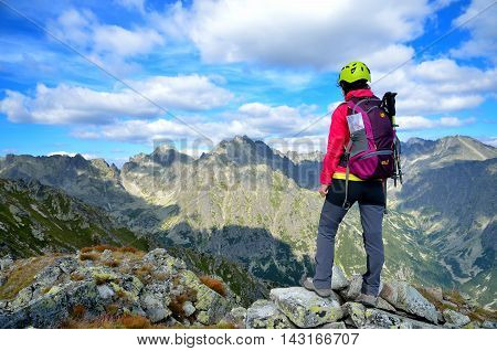 HIGH TATRA SLOVAKIA - AUGUST 20 2015: Tourist in the mountains. Young woman admiring views in High Tatra Slovakia.