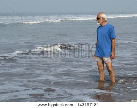 An elderly Indian man feeling young and contemplating his younger days on his holidays on the beach.
