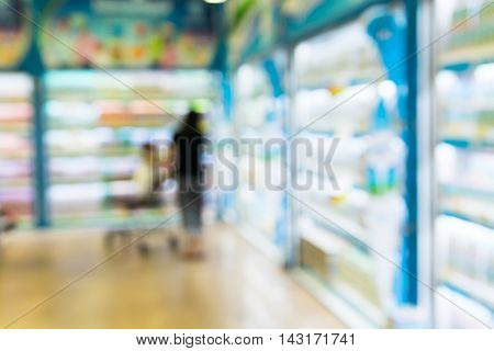 Blurred of baby on shopping cart with mother in supermarket. with baby safty sign on shoping car