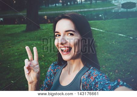 I love selfie Close up lifestyle portrait of young woman makes funny grimaces on camera. Female taking a photo self. Happy laughing emotional face. Modern life, social media concept.Brunette girl walking in park outdoor.