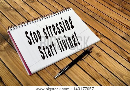 The words Stop stressing Start living on notebook