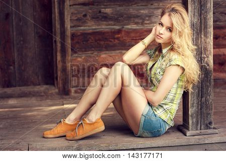 Street Style Fashion Woman Outdoors. Trendy Hipster Girl. Toned Photo with Copy Space. Wooden Background.