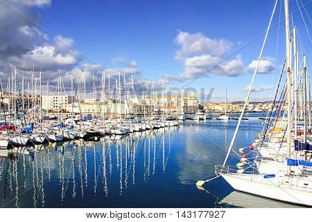 SETE, FRANCE - JANUARY 31, 2015: Boats in the harbor of of Sete with colorful reflections captured during winter. Sete - fascinating small town on the French Mediterranean coast known as the Venice of Languedoc
