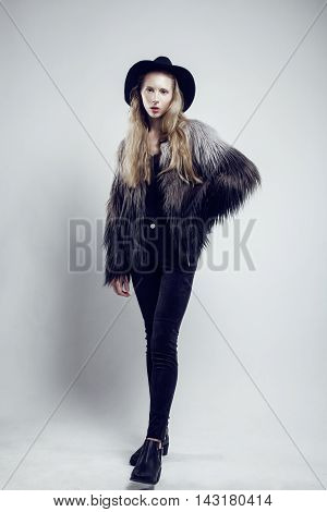 young blonde teenage girl in hat and fur coat, fashion dressed model, studio shot, modern lifestyle concept