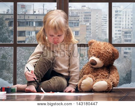 Little girl draws paints and brush. A huge window behind the glass city snow winter. toy teddy bear sitting next to. The concept of child development safety seasons panoramic windows