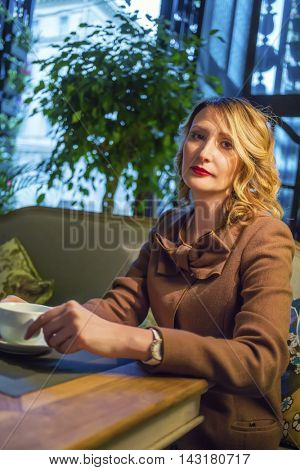 Middleaged blonde woman sits with tea and looks at camera in restaurant