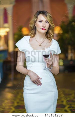 Beautiful middleaged woman in white stands with wine in restaurant, shallow dof