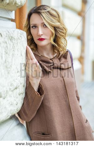 Blonde middleaged woman in jacket poses near building wall outdoor, shallow dof