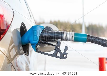 Gas pump nozzle in fuel tank of anew car, refuel