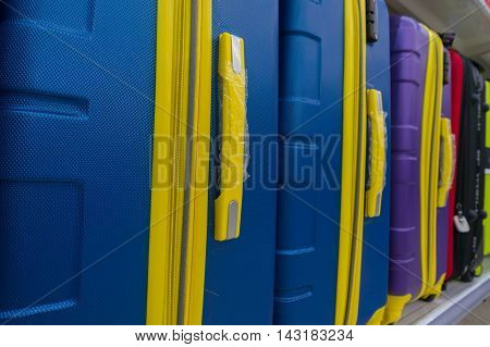 Blue And Yellow Suitcases Or Travel Bag In A Row On Shelf
