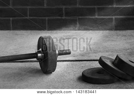 Iron barbell dumbbell bar on a wooden background against wall