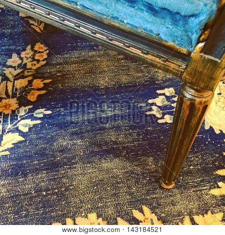 Detail of a vintage style furniture and carpet in blue in yellow colors.