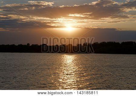 Sunset ove Volga river in Russia. Orange clouds in sunset time. Nightfall.