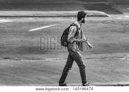 MONTEVIDEO, URUGUAY, NOVEMBER - 2015 - Black and white urban scene of young man walking on the street of Montevideo Uruguay