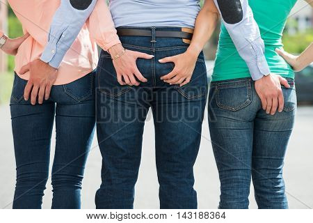 Rear View Of Friends Holding Each Other's Buttock
