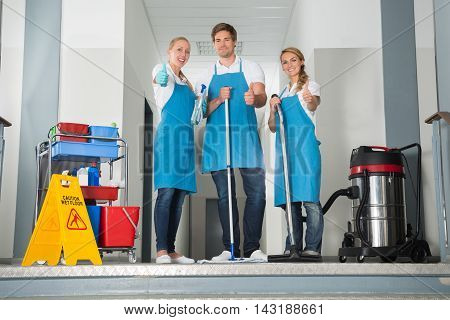 Group Of Happy Young Janitor With Cleaning Equipment Showing Thumbs Up