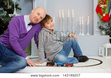 Happy father and son play with toy train near christmas tree and candles