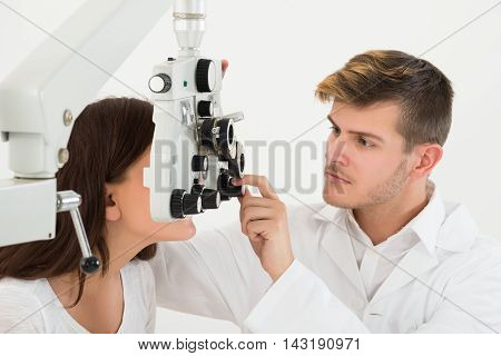 A Male Ophthalmologist Adjusting The Panel Of Phoropter While Examining Female Patient's Eyes