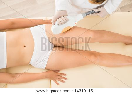 Close-up Of A Male Therapist Giving Laser Epilation Treatment To Young Woman's Leg