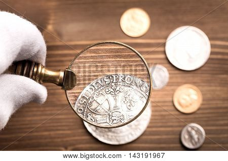 Examining antique silver coin through magnifying glass on wooden table
