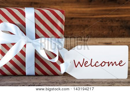 Macro Of Christmas Gift Or Present On Wooden Background. Card For Seasons Greetings, Best Wishes Or Congratulations. White Ribbon With Bow. English Text Welcome