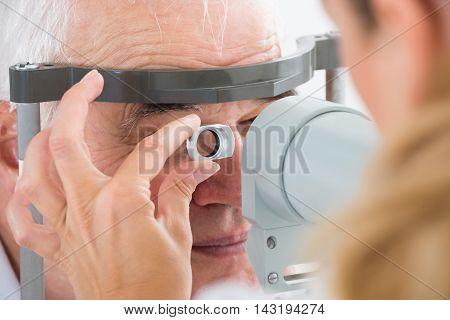 Close-up Of Senior Man Checking Eyesight In Clinic
