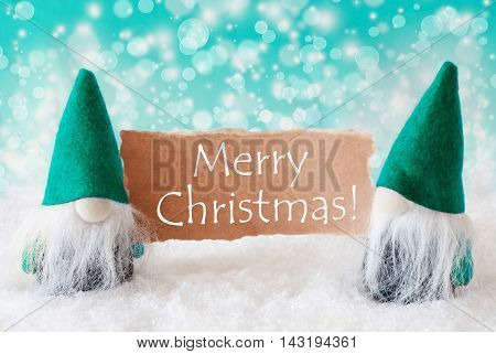 Christmas Greeting Card With Two Turqoise Gnomes. Sparkling Bokeh Background With Snow. English Text Merry Christmas