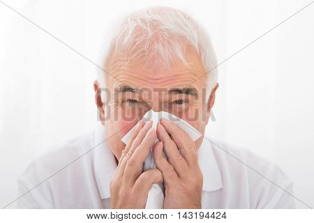 Close-up Of Senior Man Infected With Cold Blowing His Nose In Clinic