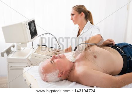 Senior Man Getting Ultrasound Scan On Neck By Young Female Doctor