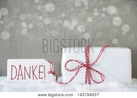 One Christmas Gift Or Present On Snow. Cement Wall As Background With Bokeh. Modern And Urban Style. Card For Birthday Or Seasons Greetings. Label With German Text Danke Means Thank You