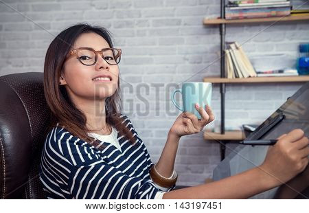 Asian woman looking down on a cup of coffee to sketchhapy mood focus on face