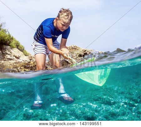 Young boy exloring costal nature in the rocky sea with a fishing net.