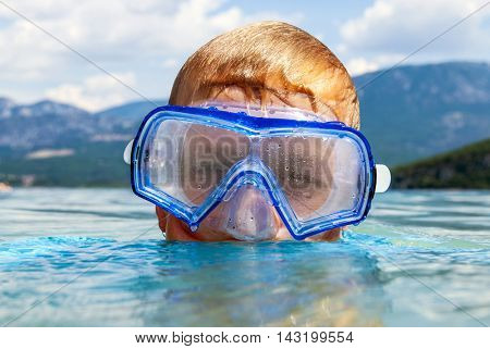 Young boy, with his head just above the surface, wearing a scuba mask in a lake