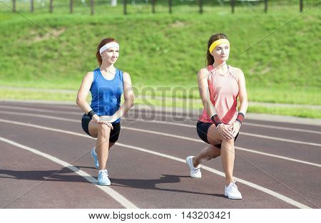 Sport Fitness and Workout Concepts and Ideas. Two Caucasian Girlfriends Having Stretching Exercises On Sport Venue Outdoors. Horizontal Image Orientation