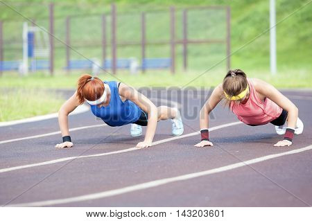 Sport Concepts and Ideas. Two Professional Female Athletes Doing Pressing Ups At Sport Venue Outdoors. Horizontal Image