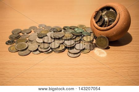 Broke Earthenware Jur with coin money on wood background