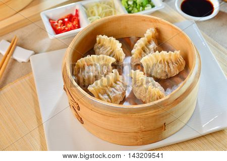 Shark fin dumplings in bamboo tray with chili and soyal sauce on white plate