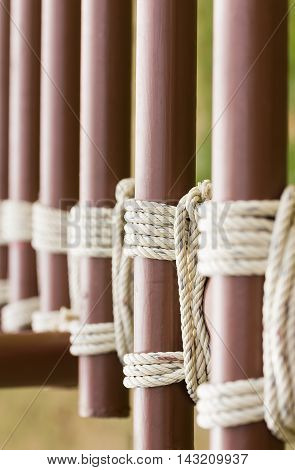 Close up of rope knot around a metal fence Rope tied knot metal pipe pole