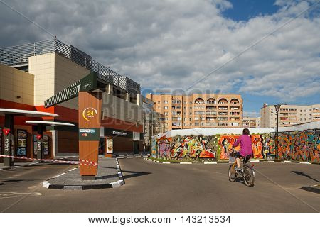 Dubna Russia - Jul 21 2014: Daytime street view of the city with a woman riding bike.